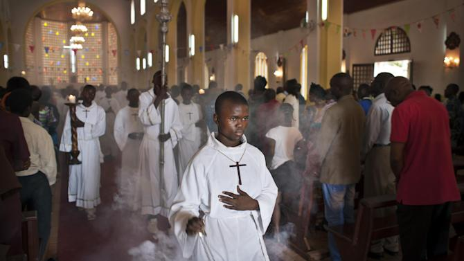 The thurifer swings the thurible of incense as he leads the procession out of the Notre Dame Cathedral of the Immaculate Conception at the end of the morning mass in Bangui, Central African Republic Sunday, Jan. 6, 2013. Rebels in Central African Republic seized control of another town on Saturday, just days before they are to begin negotiations with the government, casting doubt on the possible success of the talks. (AP Photo/Ben Curtis)