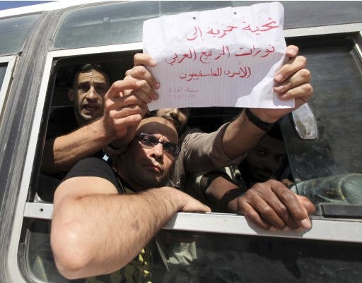A Palestinian prisoner holds a sign as he enters Gaza with other prisoners via the Rafah crossing from Egypt