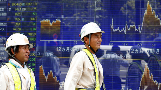 Workers walk past an electronic stock indicator in Tokyo, Friday, Aug. 10, 2012. Asian stock markets floundered Friday, as traders displayed caution ahead of the release of trade data from China. Japan's Nikkei 225 index fell 0.6 percent to 8,924.82. (AP Photo/Shizuo Kambayashi)