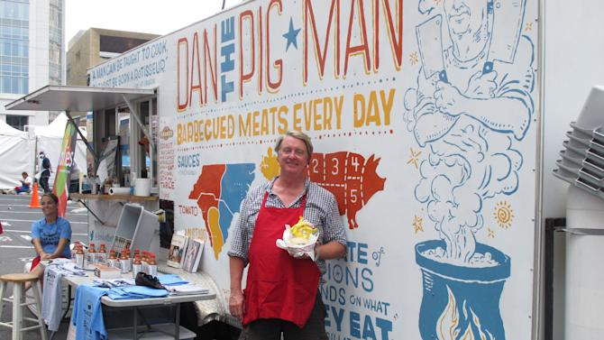 """Dan Huntley, also known as """"Dan the Pig Man"""" holds up one of his barbecue sandwiches outside his food truck in Charlotte, N.C. on Tuesday, Sept. 4, 2012. Huntley had his best day ever during the convention, selling $10,000 worth of sandwiches. (AP Photo/Jeffrey Collins)"""