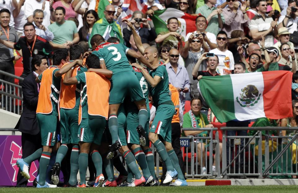 Mexico players celebrate a goal by teammate Oribe Peralta during the men's soccer final against Brazil at the 2012 Summer Olympics, Saturday, Aug. 11, 2012, in London. (AP Photo/Hassan Ammar)