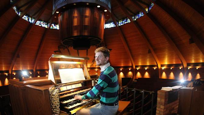 Organist Christopher Keady sits at the circular pipe organ at the Agnes Flanagan Chapel Tuesday, June 12, 2012, on the campus of Lewis & Clark College, in Portland, Ore. The Agnes Flanagan Chapel is a 16-sided architectural marvel that seats 650 under stained glass windows depicting the book of Genesis. In the early 1970s, it was also a big, conical quandary. Chapels aren't really chapels unless they have an organ, and the newly-minted structure at Portland's Lewis & Clark College was in need.  (AP Photo/Rick Bowmer)