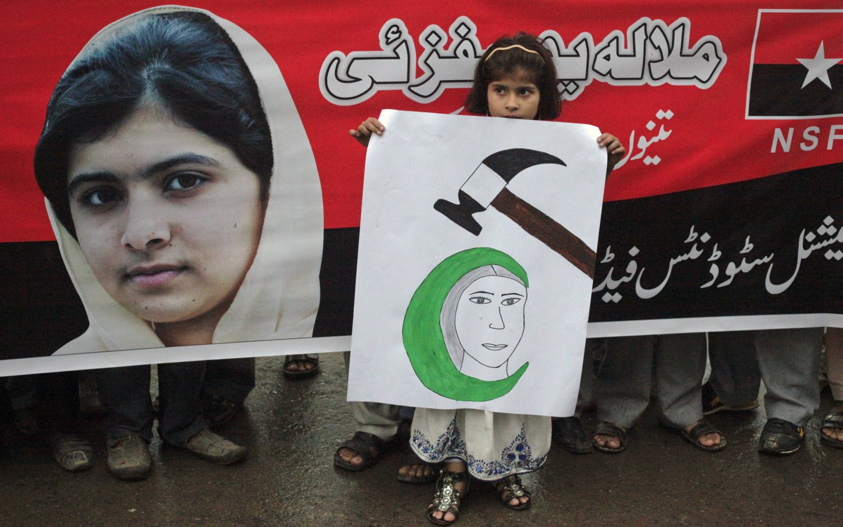 A girl holds a placard next to an image of schoolgirl Malala Yousufzai, who was shot on October 9 by the Taliban, during a rally organized by National Students Federation (NSF) in Lahore October 15, 2012. Yousufzai, 14, who was shot by Taliban gunmen for pushing for girls to be educated, has been sent to the United Kingdom for medical treatment, a military spokesman said on Monday.