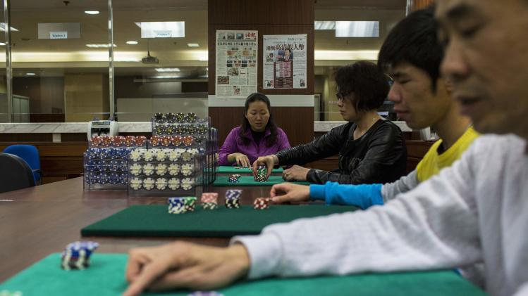 Students count chips during a gaming lesson at a mock casino run by the MPI Gaming Teaching and Research Centre in Macau