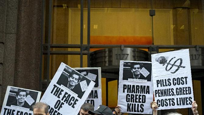 FILE - In this Thursday, Oct. 1, 2015, file photo, activists hold signs containing the image of Turing Pharmaceuticals CEO Martin Shkreli in front the building that houses Turing's offices, in New York, during a protest highlighting pharmaceuticaldrug pricing. After weeks of criticism from patients, doctors and even other drugmakers for hiking a life-saving medicine's price more than fiftyfold, Turing Pharmaceuticals is reneging on its pledge to cut the $750-per-pill price. But a competitor's 99-cent capsule version is selling well. (AP Photo/Craig Ruttle, File)