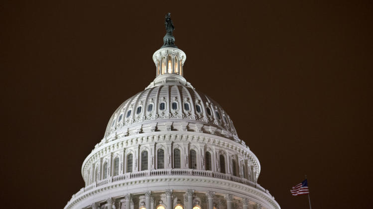 "As an evening haze lights the sky with a reddish glow, the lights of the U.S. Capitol burn into the night as the House continues to work on the ""fiscal cliff"" legislation proposed by the Senate, in Washington, on Tuesday, Jan. 1, 2013. (AP Photo/Jacquelyn Martin)"