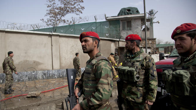 Afghan Army soldiers take position at the gate of the Afghan Defense Ministry after a suicide bomber on a bicycle struck outside the ministry, killing at least nine Afghan civilians as U.S. Defense Secretary Chuck Hagel visited Kabul, Afghanistan, Saturday, March 9, 2013.  (AP Photo/Anja Niedringhaus)