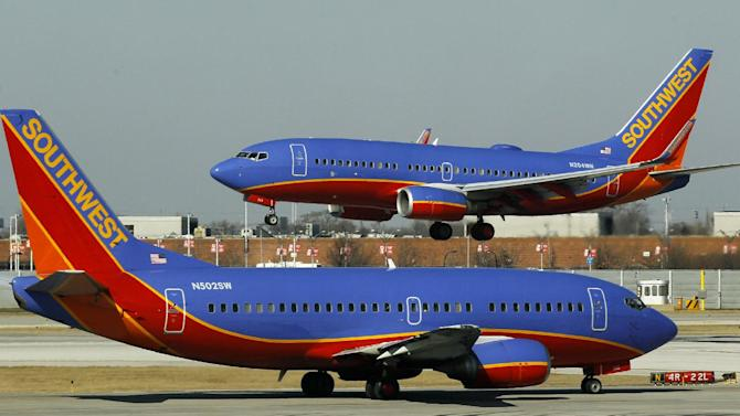 In this Feb. 9, 2012 file photo, a Southwest Airlines Boeing 737 waits to take off at Chicago's Midway Airport as another lands. A spokesman for Southwest Airlines says all departing flights have been grounded due to a system-wide computer problem, Saturday, June 22, 2013. (AP Photo/Charles Rex Arbogast)