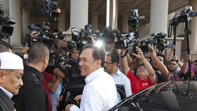 Malaysian opposition leader Anwar Ibrahim, center, is surrounded by media as he arrives at the High Court to face charges of participating in an illegal street protest in Kuala Lumpur, Malaysia, Tuesday, May 22, 2012. (AP Photo/Mark Baker)