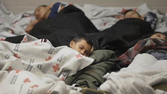 FILE - This June 18, 2014, file photo, detainees sleep in a holding cell at a U.S. Customs and Border Protection, processing facility in Brownsville,Texas. Immigration courts backlogged by years of staffing shortages and tougher enforcement face an even more daunting challenge since tens of thousands of Central Americans began arriving on the U.S. border fleeing violence back home. For years, children from Central America traveling alone and immigrants who prove they have a credible fear of returning home have been entitled to a hearing before an immigration judge. (AP Photo/Eric Gay, Pool, File)
