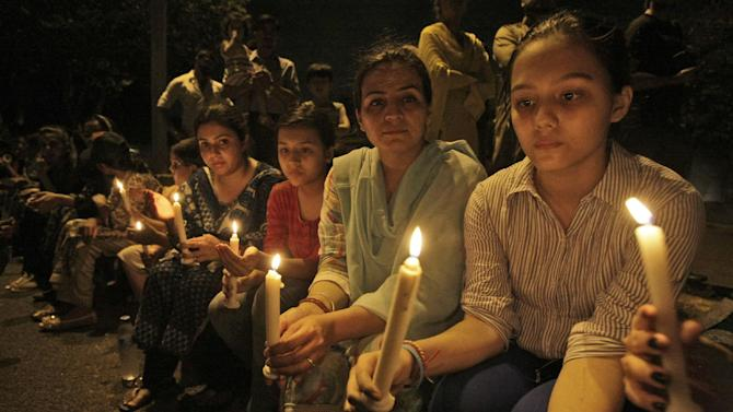 Pakistanis hold candles during a protest to condemn the killing of Zohra Shahid, a senior member of former Pakistani cricket star Imran Khan's Pakistan Tehreek-e-Insaf party in Sindh, in Karachi, Pakistan, Sunday, May 19, 2013. Police said gunmen on a motorcycle shot and killed Shahid outside her home on Saturday, May 18, 2013, in the city of Karachi in southern Sindh province. (AP Photo/Fareed Khan)
