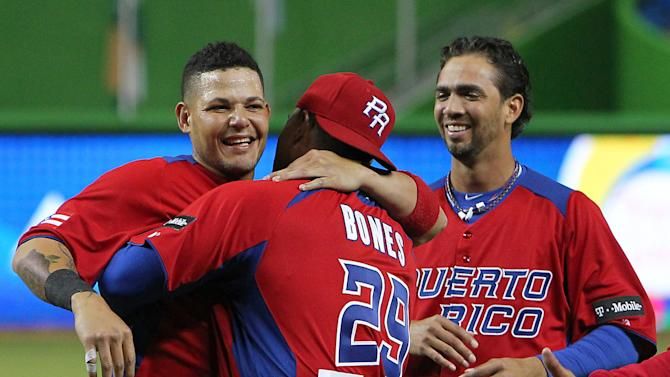 Puerto Rico catcher Yadier Molina ,left, pitching coach Rick Bones,center, and pitcher Nelson Figueroa celebrate after defeating the USA 4-3 in the World Baseball Classic second round Pool 2 elimination game between Puerto Rico and the United States at Marlins Park in Miami on Friday, March 15, 2013. (AP Photo/The Miami Herald, David Santiago)  MAGS OUT