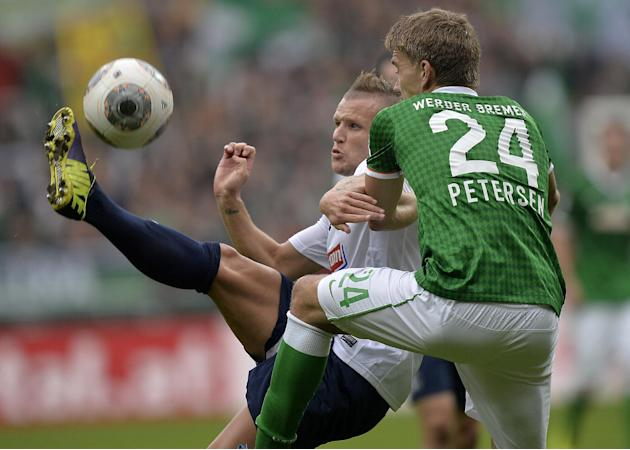 Freiburg's Jonathan Schmid of France, left, and Bremen's Nils Petersen challenge for the ball during the German first division Bundesliga soccer match between Werder Bremen and SC Freiburg in Bremen,