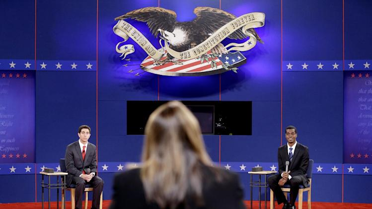 Stand-ins for Republican presidential candidate, former Massachusetts Gov. Mitt Romney, left, and President Barack Obama, right, run through a rehearsal with moderator Candy Crowley, back to camera, ahead of Tuesday's presidential debate, Monday, Oct. 15, 2012, at Hofstra University in Hempstead, N.Y. (AP Photo/David Goldman)