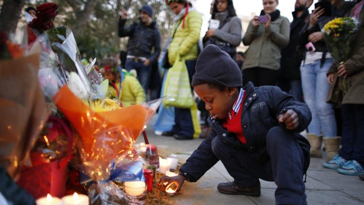 Wenceslous Nicholas lights a candle in front of the statue of former South African President Nelson Mandela in Parliament Square in central London