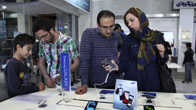 "Potential customers try out Samsung mobile phones in a store in Tehran, Iran, Thursday, April 25, 2013. Iranian users of Samsung mobile applications are saying they have been notified that their access to the company's online store will be denied from May 22. Samsung said it cannot provide access to the store in Iran because of ""legal barriers."" (AP Photo/Vahid Salemi)"