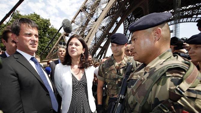 French Interior Minister Manuel Valls, left, and Junior Minister of Crafts, Business and Tourism Sylvia Pinel , second left, talk with French soldiers during a visit with journalists next to the Eiffel Tower in Paris Friday Aug. 2, 2013 during a tour focused on security at the city's top tourist areas. (AP Photo/Francois Mori)