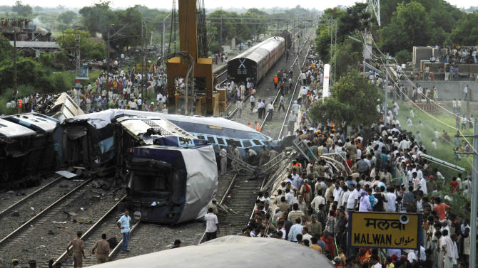 People gather around the wreckage of the Kalka Mail passenger train which derailed near the town of Fatehpur in Uttar Pradesh state, India, Sunday, July 10, 2011. The packed train was on its way to New Delhi from Howrah, a station near Kolkata, when its 12 coaches and the engine jumped the tracks. Dozens of people died and more than 100 are injured, according to officials. (AP Photo/Rajesh Kumar Singh)