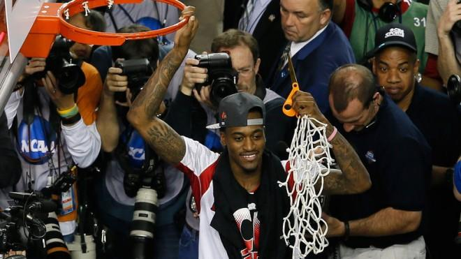 Injured Louisville guard Kevin Ware celebrates after cutting down the net after his team beat Michigan 82-76.