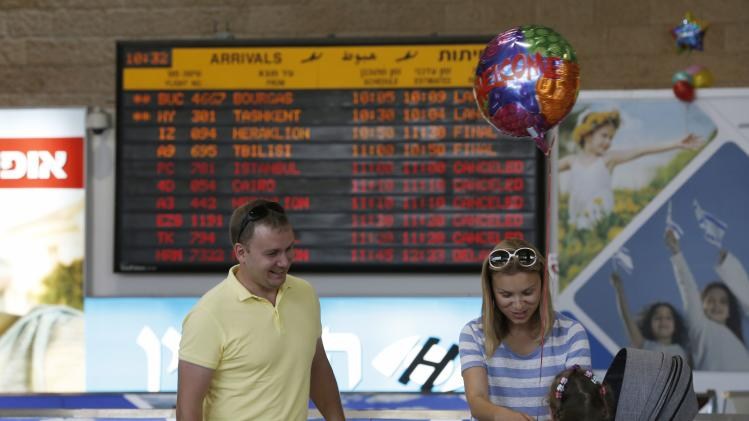 A woman ties a balloon to the hand of a girl at the arrivals hall at Ben Gurion International airport