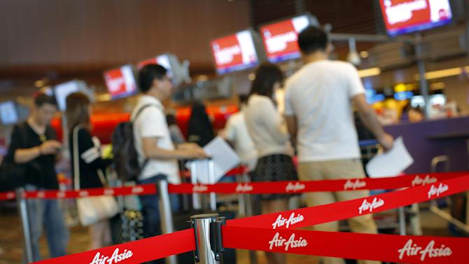 Passengers queue for their flights at the AirAsia check-in counter in Changi International Airport on Sunday, Dec. 28, 2014 in Singapore. In the third air incident connected to Malaysia this year, an AirAsia plane went missing on Sunday while flying over the Java Sea after taking off from a provincial city in Indonesia for Singapore. (AP Photo/Wong Maye-E)