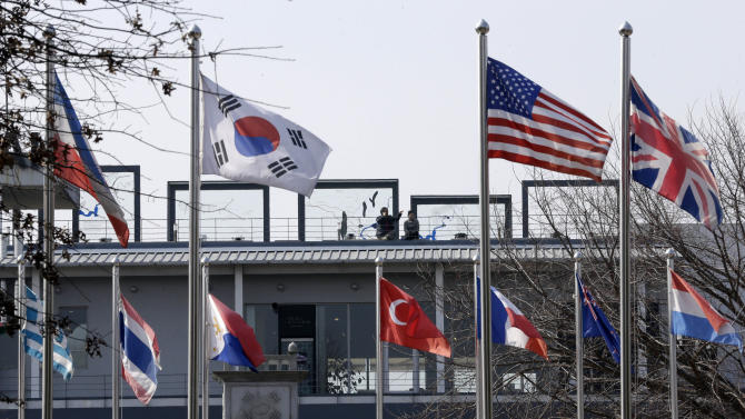 Visitors are seen through the flags at the Imjingak Pavilion near the border village of Panmunjom, which has separated the two Koreas since the Korean War, in Paju, north of Seoul, South Korea, Friday, March 15, 2013. Busloads of tourists still show up to gawk at the world's most heavily fortified border, even as governments on both sides threaten to reduce each other to rubble. (AP Photo/Lee Jin-man)