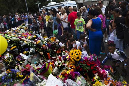 People pay tribute and place flowers outside the house where former South African President Mandela died, in Johannesburg