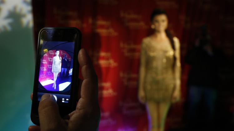 A person uses a mobile device to photograph the wax figure of singer and actress Selena Gomez after it was unveiled at Madame Tussauds museum in Hollywood