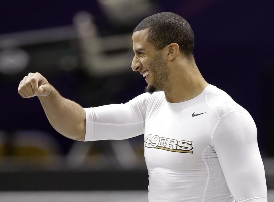 San Francisco 49ers quarterback Colin Kaepernick laughs as he walks onto the Superdome field for practice on Saturday, Feb. 2, 2013, in New Orleans. The 49ers are scheduled to play the Baltimore Ravens in the NFL Super Bowl XLVII football game on Feb. 3. (AP Photo/Mark Humphrey)