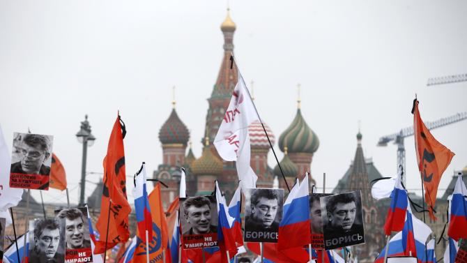 People hold flags and posters during march to commemorate Kremlin critic Nemtsov in central Moscow