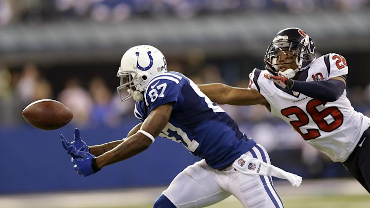 Indianapolis Colts' Reggie Wayne (87) reaches for a pass while being defended by Houston Texans' Brandon Harris (26) during the first half of an NFL football game, Sunday, Dec. 30, 2012, in Indianapolis. The pass was incomplete. (AP Photo/Michael Conroy)