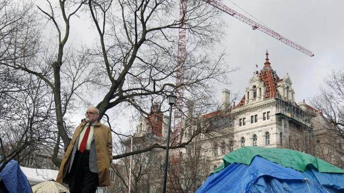 Occupy Albany protester Fred Childs of Albany, N.Y., walks in Academy Park in Albany, Thursday, Dec. 22, 2011. Occupy Albany's 24-hour permit for the park expired at 7 a.m. on Thursday but protesters and tents remained in the park. The group has events planned later in the day. (AP Photo/Mike Groll)