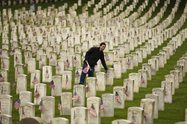 A man places a flag at a grave at Cypress Hills National Cemetery in Brooklyn, New York