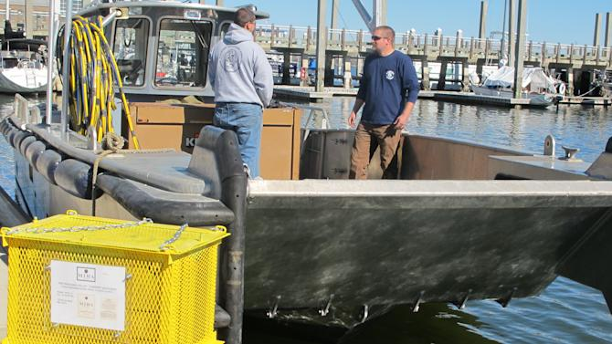 Bottles of Cabernet Sauvignon in protective steel cages, left, are ready to be loaded onto a boat in Charleston, S.C., on Wednesday, Feb. 20, 2013. Mira Winery of St. Helena, California, submerged four cases of wine in Charleston Harbor on Wednesday to see what effect the ocean has on aging the wine. Similar experiments with ocean aging have been conducted in Europe. (AP Photo/Bruce Smith)