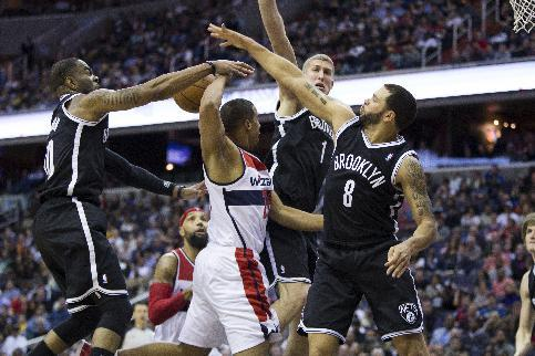 Washington Wizards guard Andre Miller passes the ball behind his head to teammate forward Drew Gooden as he is defended by, from left, Brooklyn Nets guard Marcus Thornton, forward Mason Plumlee, and g
