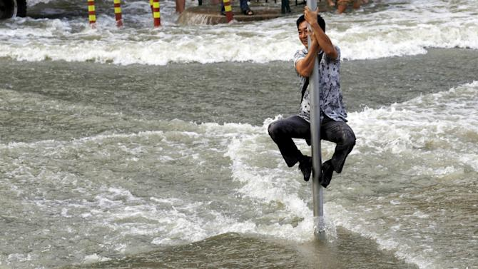 A man climbs on a road sign pole to escape the water from a tidal bore which surged past a barrier on the banks of Qiantang River, in Hangzhou