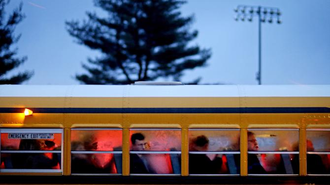 FILE - In this Dec. 16, 2012 file photo, people arrive on a school bus at Newtown High School for a memorial vigil attended by President Barack Obama for the victims of the Sandy Hook Elementary School shooting in Newtown, Conn. It was a year of storms, of raging winds and rising waters, but also broader turbulence that strained our moorings. 2012 battered us with floods and tempests, and seemed especially dark in its final days. (AP Photo/David Goldman, File)