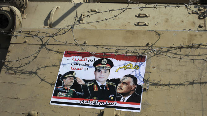 FILE - In this Sunday, Oct. 6, 2013 file photo, a poster showing Egyptian Defense Minister Gen. Abdel-Fattah el-Sissi, center, and former presidents Anwar Sadat, left, and Gamal Abdel-Nasser, right, is taped to an army armored vehicle on a bridge leading to Tahrir Square during celebrations marking the 40th anniversary of Egypt's Oct. 6 crossing of the Suez Canal during the 1973 war with Israel, in Cairo, Egypt. Under President Mohammed Morsi, his Islamist allies pushed through a constitution that alarmed many Egyptians with its new, stronger provisions for implementing Islamic Shariah law and carving out extensive power for the military. Now after Morsi's ouster, it is the turn of liberal and secular politicians to amend the charter, but they are balking at reversing those changes, caught up in the country's stormy politics. (AP Photo/Thomas Hartwell, File)