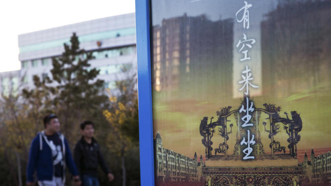 """In this photo taken on Wednesday, Oct. 24, 2012, people walk past an advertising poster depicting an emperor seat with the words """"Feel free come, have a seat"""" near the city government office in Xilinhot in northern China's Inner Mongolia. Buying and selling office is so rampant in China that it has eroded public trust in officialdom, undermining the ruling Communist Party's image as an institute that promotes the competent, not the connected. Even though Chinese leaders have vowed to eradicate the practice, it has showed no sign of abatement. (AP Photo/Andy Wong)"""