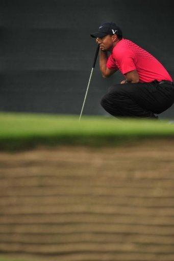 Tiger Woods of the US lines up a putt during his final round on day four