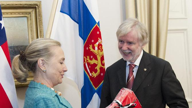 U.S. Secretary of State Hillary Rodham Clinton receives a gift from Finnish Foreign Minister Erkki Tuomioja, Wednesday, June 27, 2012, at the Government Banquet Hall in Helsinki, Finland. (AP Photo/Haraz N. Ghanbari, Pool)