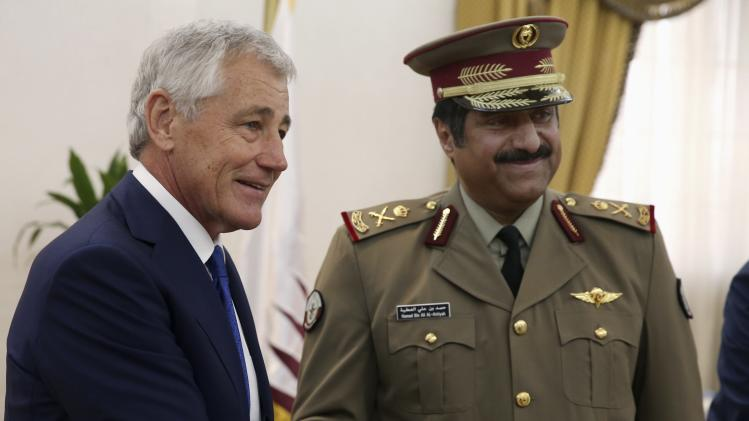 U.S. Secretary of Defense Chuck Hagel shakes Qatari Defence Minister Hamad bin Ali al-Attiyah (R) at the Defense Headquarters in Doha