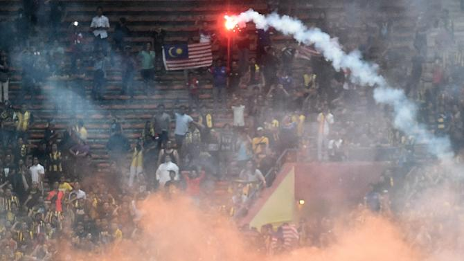 Yasyn Alnakhli of Saudi Arabia walks off the pitch after flares were thrown on the pitch during the 2018 World Cup qualifying football match between Malaysia and Saudi Arabia in Shah Alam on September 8, 2015