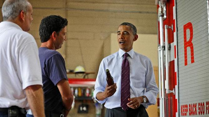 President Barack Obama holds up a bottle of beer as he delivers a case of White House brewed beer to the fire fighters at Fire Station No. 14, during an unscheduled stop, Tuesday, Sept. 4, 2012, in Norfolk, Va. (AP Photo/Pablo Martinez Monsivais)