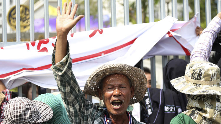 A Thai farmer raises his arm during a rally to demand the government to speed up the payment for the price of their crops outside the Commerce Ministry in Bangkok Thursday, Feb. 6, 2014. An ambitious rice buying program that Thailand's ruling party hoped would uplift millions of its poor rural supporters may end up helping to bring down the increasingly cornered government. (AP Photo/Apichart Weerawong)