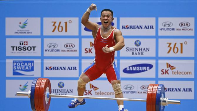 North Korea's Om reacts after successfully lifting his second attempt in the men's 56kg clean and jerk weightlifting competition during the 17th Asian Games in Incheon