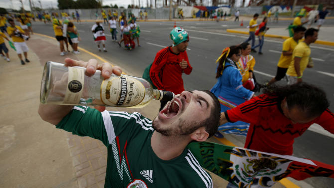 In this Tuesday, June 17, 2014 photo, Mexican fans drinks tequila outside of the Arena Castelao before the World Cup group A soccer match between Brazil and Mexico in Fortaleza, Brazil. Many of the soccer fans traveling from the U.S. to Brazil, are part of the last great wave of Mexican migration to the United States, which spanned the 1990s to the mid-2000s. Others are second-generation Mexicans who grew up rooting for the Mexican team at a time when Team USA was still unknown. (AP Photo/Eduardo Verdugo)