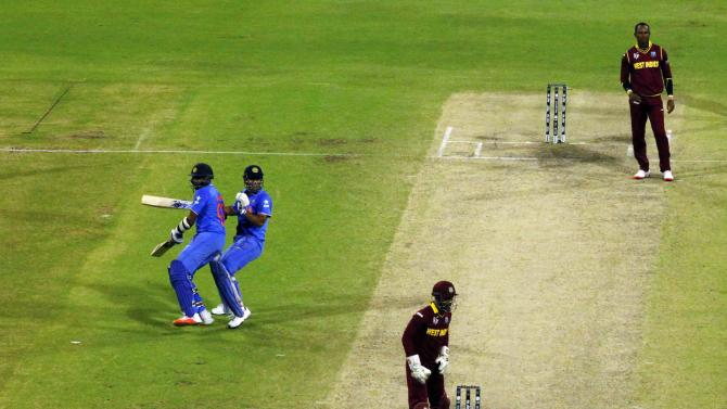 India's batsmen Ravichandran Ashwin and MS Dhoni collide on the pitch as they gather runs during their win against the West Indies at the Cricket World Cup in Perth