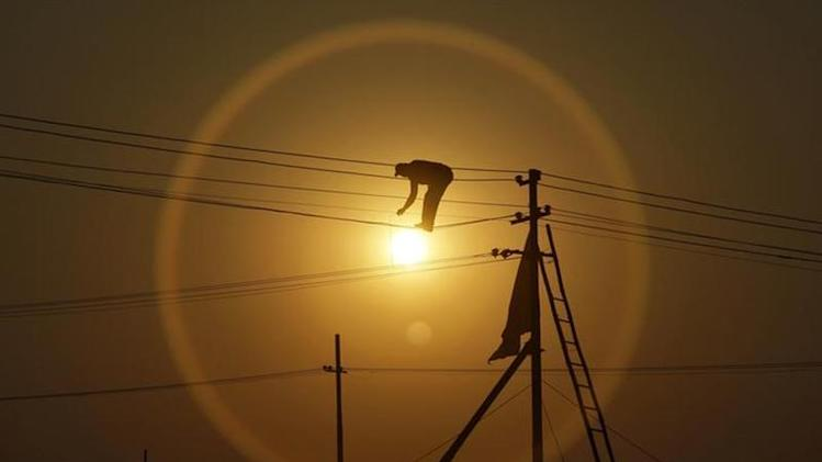 "An employee from the electricity board works on newly installed overhead power cables ahead of the ""Kumbh Mela"", or Pitcher Festival, as the sun sets in Allahabad December 7, 2012. REUTERS/Jitendra Prakash/Files"