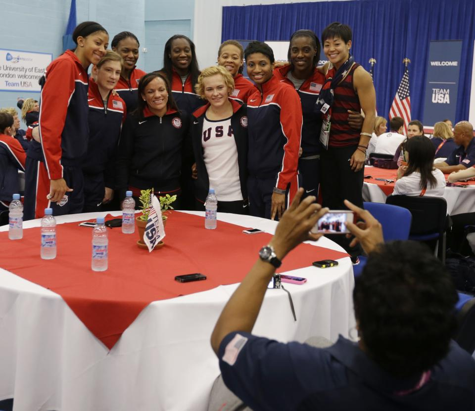 Members of Team USA pose for photos before First lady Michelle Obama speaks during a breakfast at the 2012 Summer Olympics, Friday, July 27, 2012, in London. (AP Photo/Darron Cummings)